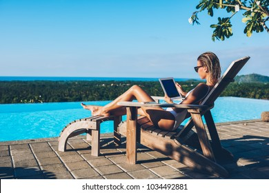 Sexy young woman in swimsuit and sunglasses reading e-book while sunbathing on sun bed near pool enjoying summer holidays. Female tourist using tablet for distance job while resting in resort spa