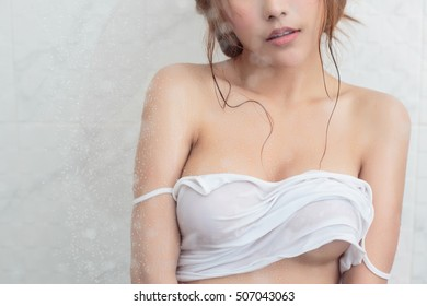 sexy young woman taking a shower with white tank top