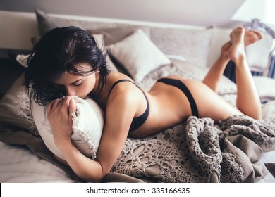 Sexy young woman in underwear lying in bed on his stomach, embraced pillow, partially naked.