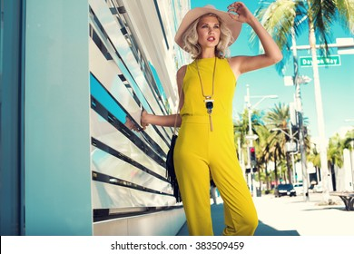 Sexy young woman walking in a city in yellow jumpsuit, nude hat, necklace, black handbag. Fashion summer photo. Bright colors