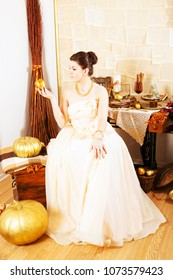 sexy young woman wearing full-length ball gown with golden apple sitting