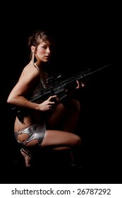 Sexy young woman wearing a silver dress and holding an assault rifle.