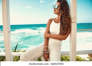 Sexy young woman in white clothes posing in the garden by the sea. Fashion summer photo. Bright colors, sunglasses
