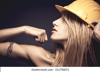 Sexy young woman with yellow safety helmet showing muscles against violet background