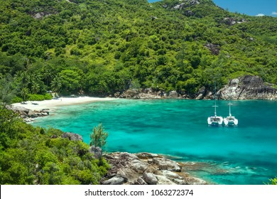 Seychelles - Mahe island - Remote secluded beach Anse Major surrounded by bright jungle mountain nature with turquoise warm waters of Indian ocean  and two white yacht