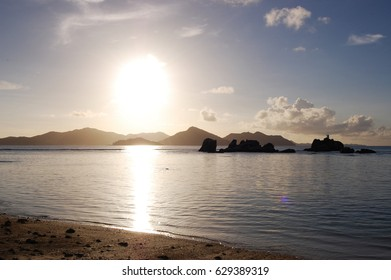Seychelles mountains silhouette on a wild beach  clouds with a strong sun light