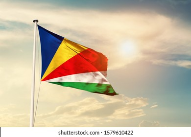 Seychelles national flag cloth fabric waving on the sky with beautiful sun light - Image