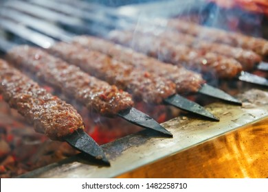 Seyhan, Adana / Turkey - 08/06/2019 : Traditional Turkish Adana Kebab or Kebap on the grill with skewers in the restaurant for dinner