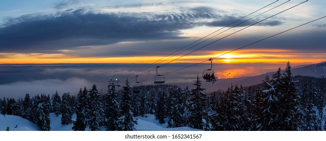Seymour Mountain, North Vancouver, British Columbia, Canada. Panoramic View of Chairlift going up to the top of a ski resort during a sunny and cloudy winter sunset.
