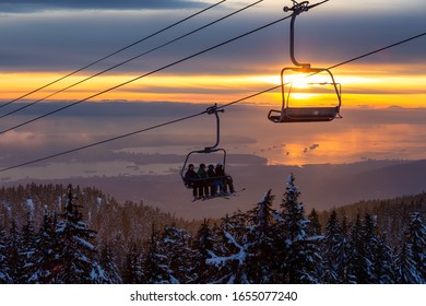 Seymour Mountain, North Vancouver, British Columbia, Canada - Feb 10, 2020 - Chairlift going up to the top of a ski resort during a sunny and cloudy winter sunset.