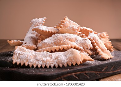 Sfrappole or chiachiere or angel wings on a woody background. Italian Carnival and TYPICAL food. Traditional sweet crisp pastry deep-fried and sprinkled with powdered sugar. Copy space