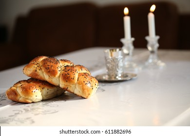 Shabbat candles in glass candlesticks with blurred covered challah background. Isolated on black. Copy space.