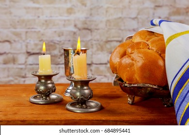 Shabbat candles in glass candlesticks with blurred covered challah background.
