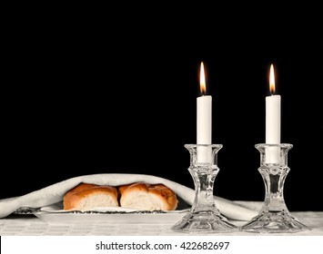 Shabbat candles in glass candlesticks isolated on black. Blurred background of covered challah bread in silver tray on white tablecloth. Copyspace.
