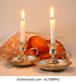 shabbat image. challah bread and candles on wooden table