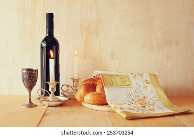 shabbat image. challah bread, wine and candelas on wooden table.