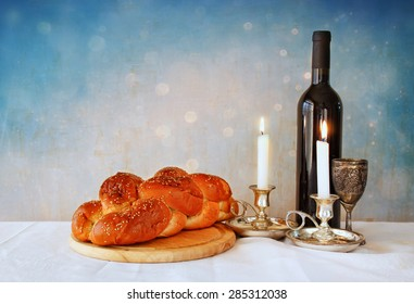 shabbat image. challah bread, shabbat wine and candelas on wooden table. glitter overlay