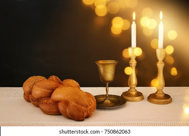 shabbat image. challah bread, shabbat wine and candles on the table.