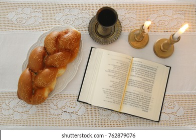 shabbat image. challah bread, shabbat wine and candles on the table. Top view