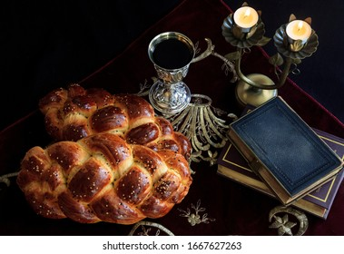 Shabbat image, challah breads, wine and candles on the table.
