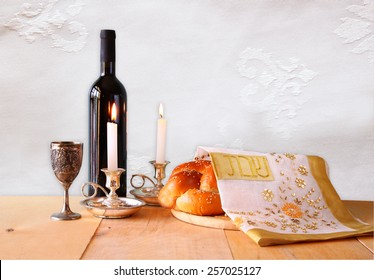 shabbat image. challah bread,wine and candelas on wooden table.