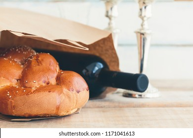 Shabbat or Sabbath grocery shopping composition with a traditional sweet fresh loaf of challah bread with a bottle of red kosher wine on a vintage wood background
