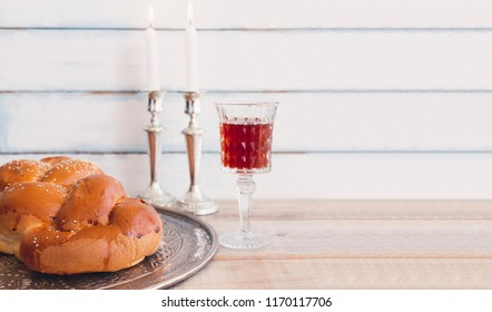 Shabbat or Sabbath kiddush ceremony composition with a traditional sweet fresh loaf of challah bread, glass of red kosher wine and candles on a vintage wood background with copy space