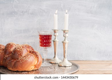 Shabbat or Sabbath kiddush ceremony composition with a traditional sweet fresh loaf of challah bread, glass of red kosher wine and candles on a vintage wood table with copy space
