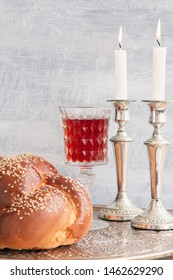 Shabbat or Sabbath kiddush ceremony composition with a traditional sweet fresh loaf of challah bread, glass of red kosher wine and candles on a vintage wood table