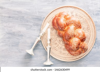 Shabbat or Sabbath kiddush ceremony composition with a traditional sweet fresh loaf of challah bread, vintage background with copy space. Overhead view, top view or above view comoisition
