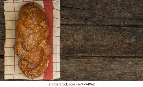 Shabbat or Sabbath kiddush ceremony composition with a traditional sweet fresh loaf of challah bread on a vintage wood background with copy space