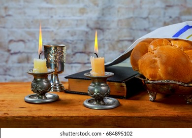 Shabbat or Sabbath kiddush ceremony composition with red kosher wine and a traditional sweet fresh loaf of challah bread on a vintage wood background with