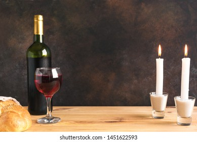 Shabbat or Shabath concept. Challah bread, shabbat wine and candles on table, copy space. Traditional Jewish Shabbat ritual.