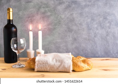 Shabbat or Shabath concept. Challah bread, shabbat wine, book and candles on table, copy space. Traditional Jewish Shabbat ritual.