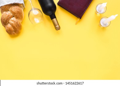 Shabbat or Shabath concept. Challah bread, shabbat wine, book and candles on yellow, top view, copy space. Traditional Jewish Shabbat ritual.