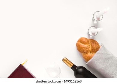 Shabbat or Shabath concept. Challah bread, shabbat wine, book and candles, top view, copy space. Traditional Jewish Shabbat ritual. Shabbat Shalom.