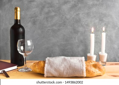 Shabbat or Shabath concept. Challah bread, shabbat wine, book and candles, copy space. Traditional Jewish Shabbat ritual. Shabbat Shalom.