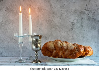 Shabbat Shalom - challah bread, shabbat wine and candles on wooden table.