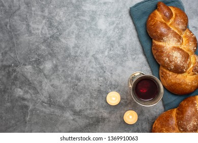 Shabbat Shalom - challah bread, shabbat wine and candles on grey background. Top view. With copy space.