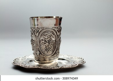 Shabbat silver kiddush cup overflowing with red wine close up. Room for text. Copy space. Isolated object.