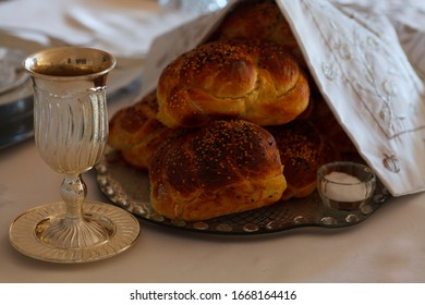 Shabbat table with kiddush cup and challah breads.