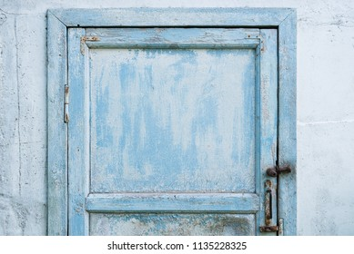 Shabby background with a blue door.