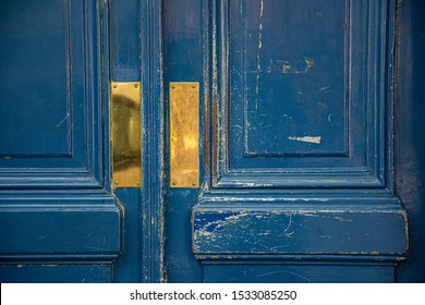 Shabby blue painted wooden door panels closeup. Shiny gold colored metal plates on rough aged wood surface of doorway. Antique textures. Architectural details of Paris door of old building in France.