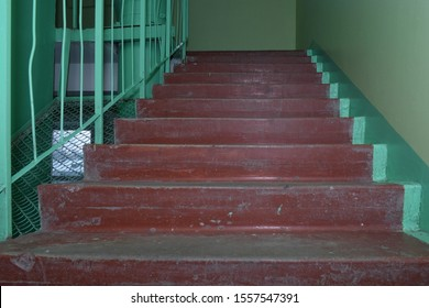 Shabby brown concrete staircase in the corridor of an old multistory building. Dirty worn flight of stairs and green walls. Low angle bottom view. Selective focus