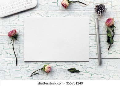 Shabby chic, boho mockup for presentations with dry roses. Desktop workplace designer, artist, painter top view. Modern trend template for advertising.