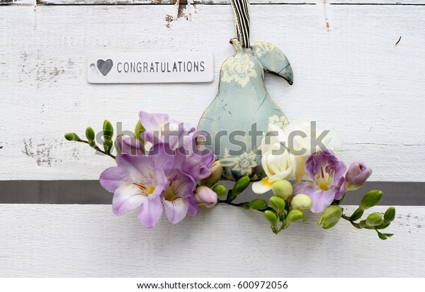 Shabby chic congratulations sign with metal pear and freesia flowers on a vintage wooden crate, wedding decoration