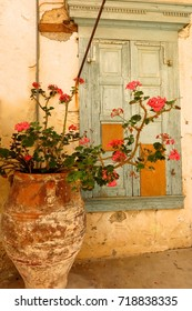 Shabby chic faded window shutters and flower pot in Kritsa village, Crete, Greece