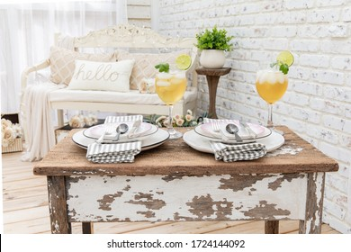 Shabby Chic garden structure with table setting for two. Visually inviting architectural design elements, natural light, white brick wall, and vintage appeal