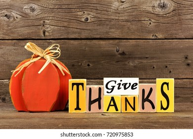 Shabby chic Give Thanks wood sign and pumpkin against a rustic wooden background