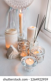 Shabby chic home design. Beautiful decoration table with a candles, dreamcacher and aroma stick on the windowsill, mindfullness relax concept